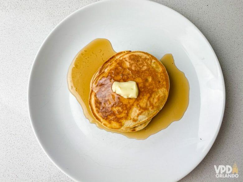 Você também vai precisar de maple syrup, manteiga, nutella ou o que mais quiser usar pra servir a sua panqueca! Foto de um prato branco com duas panquecas americanas, com um pouco de manteiga em cima e xarope de maple embaixo.