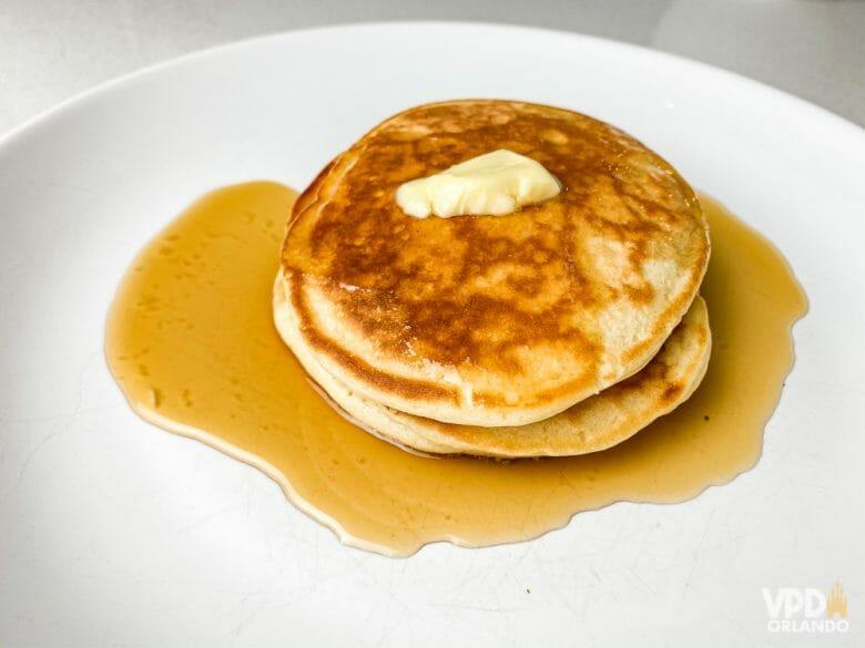 A panqueca americana é uma das melhores comidas de café da manhã! A imagem mostra um prato com duas panquecas americanas com um pouco de manteiga em cima e xarope de maple embaixo.