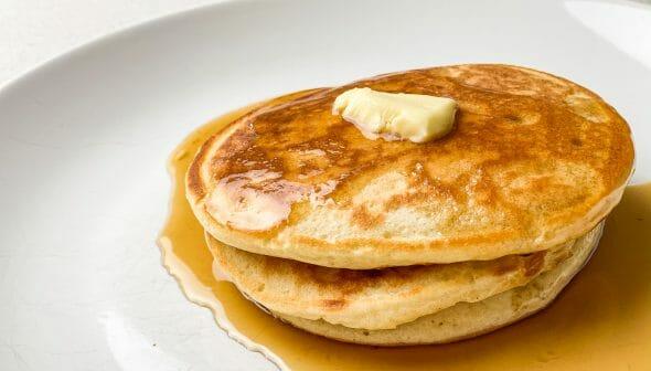 A imagem mostra um prato com duas panquecas americanas com um pouco de manteiga em cima e xarope de maple embaixo.