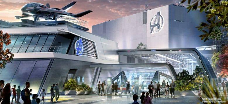 Imagem do conceito artístico do Avengers Campus divulgada pela Disney, que mostra os prédios dos Vingadores, com o Quinjet em cima e visitantes ao redor.