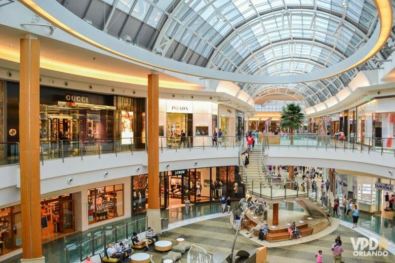 Imagem de um shopping. O centro do shopping tem visitantes caminhando e é possível ver as lojas de dois andares, bem como a abóbada transparente que permite a iluminação.