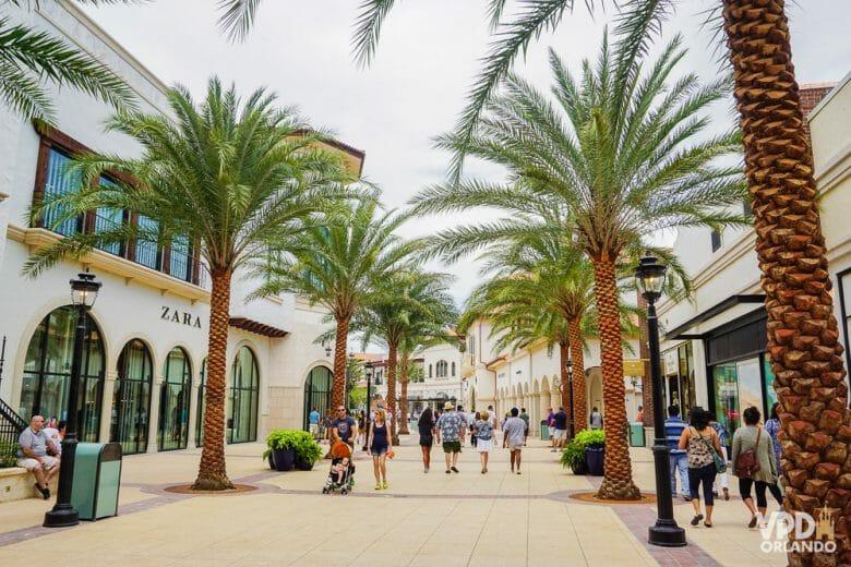 A área do Town Center parece até um outlet, de tantas lojas incríveis. Foto do centro de Disney Springs, rodeado de lojas, com palmeiras e visitantes passeando.