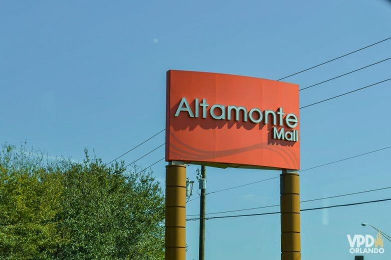 Um dos shoppings alternativos próximos a Orlando. Imagem da placa do Altamonte Mall em vermelho, com o céu azul e árvores ao fundo.