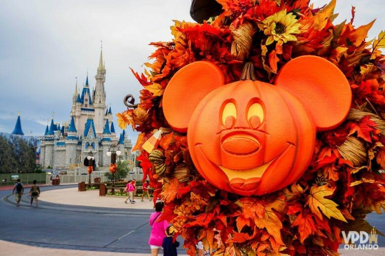 Foto da decoração de Halloween da festa do Magic Kingdom, uma abóbora em formato de Mickey iluminada por dentro. O castelo da Cinderela é visível ao fundo da foto, assim como alguns visitantes.