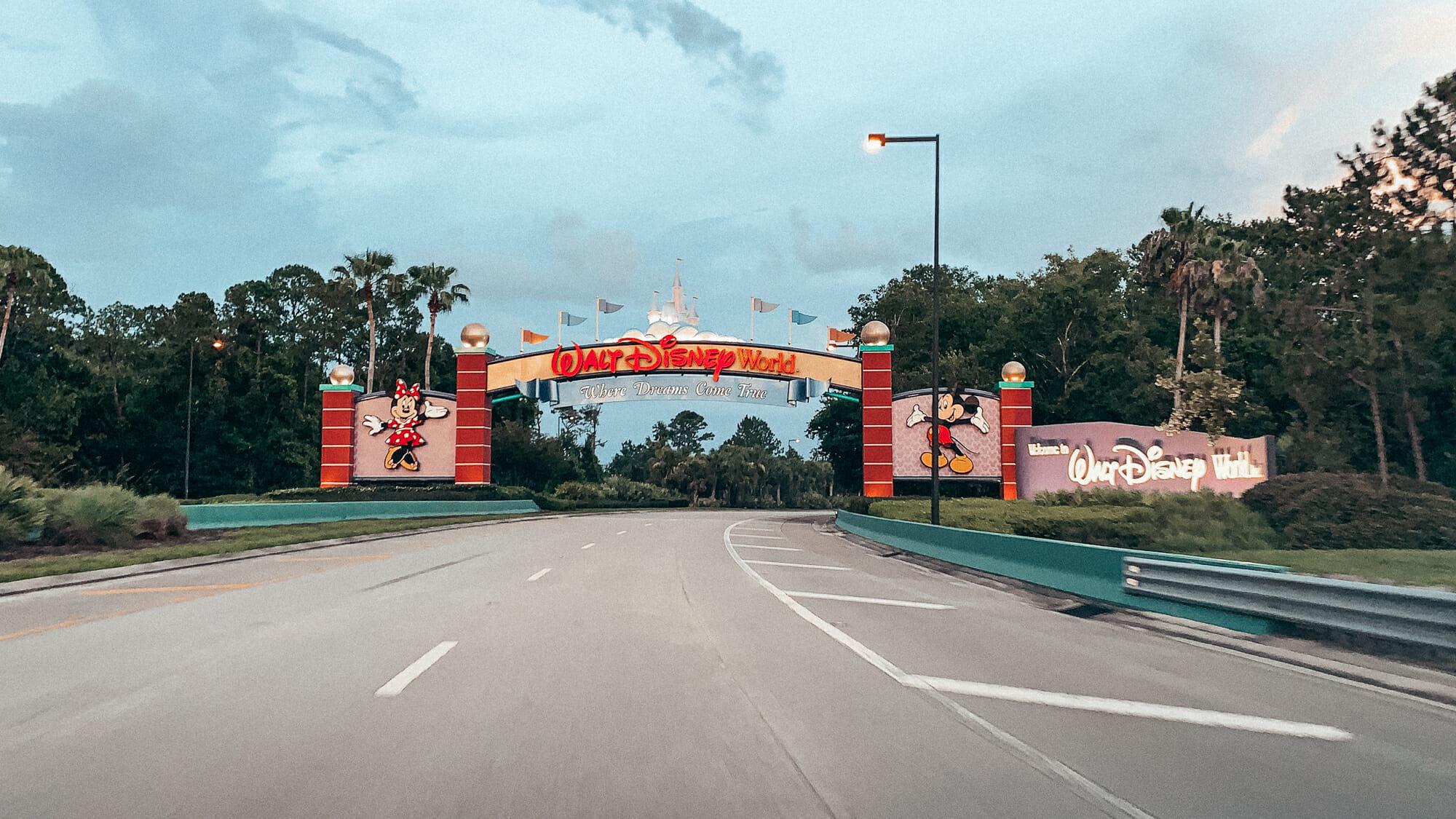 """Foto da entrada do complexo Disney em Orlando. Há um arco decorado com o Mickey e a Minnie de cada lado e as palavras """"Walt Disney World"""" acima"""