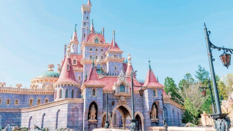 Imagem da nova área temática da Bela e a Fera na Disneyland de Tóquio, mostrando o castelo da Fera, pintado de lilás e com telhas cor-de-rosa.