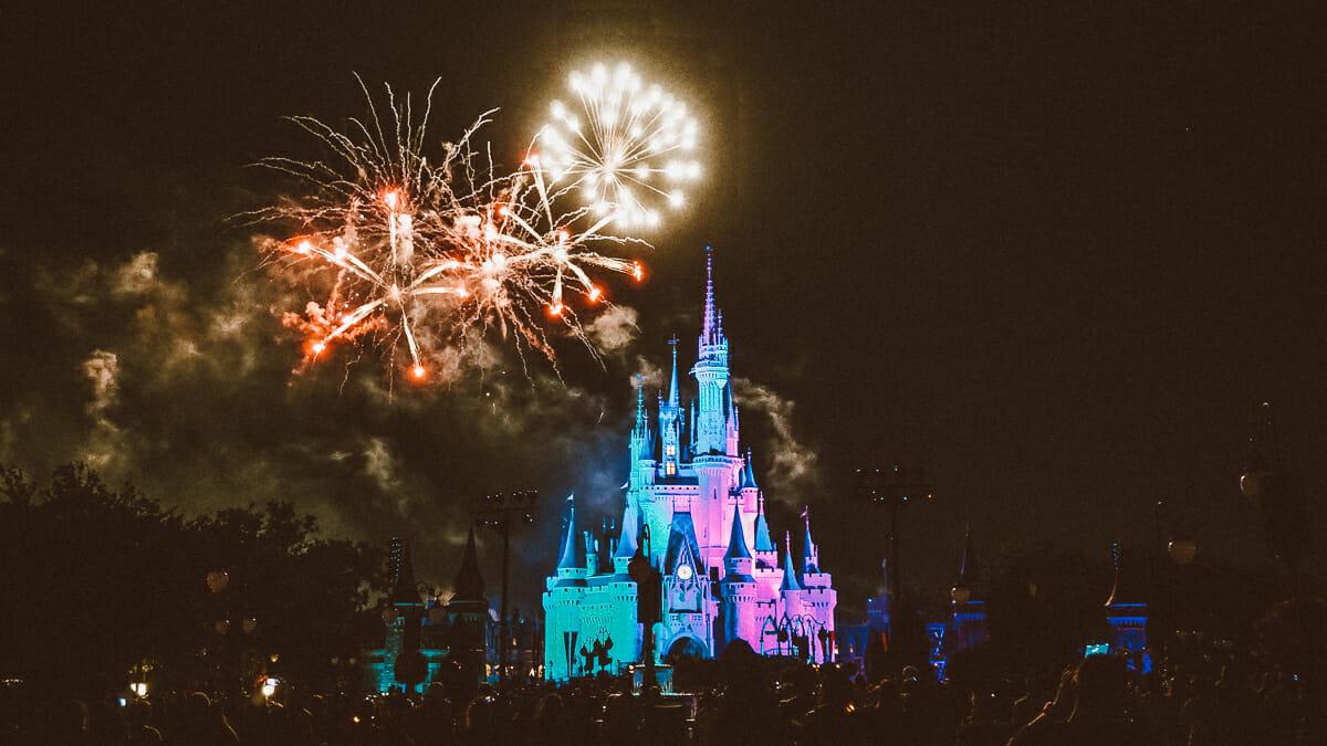 Imagem do Castelo da Cinderela no Magic Kingdom à noite, iluminado pelos fogos ao fundo e pelas luzes coloridas.