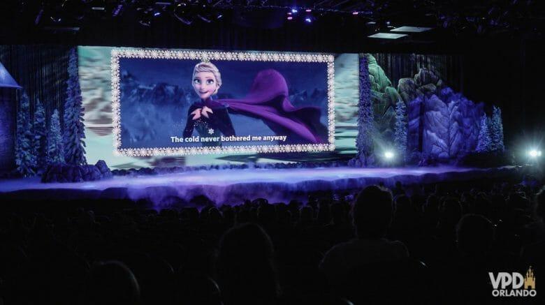 Imagem do palco durante o show de Frozen apresentado no Hollywood Studios, com a rainha Elsa no telão e a legenda para que os visitantes cantem junto.