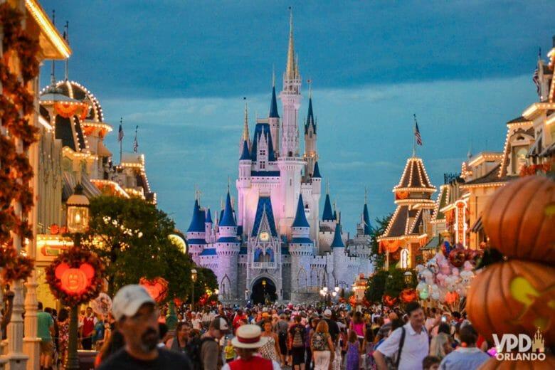 Imagem da Main Street do Magic Kingdom, cheia de visitantes e decorada com abóboras para o Halloween e o castelo da Cinderela ao fundo.
