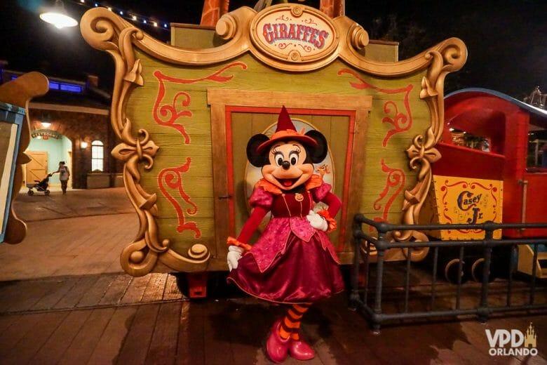Imagem da Minnie posando em frente a uma carruagem na festa do Magic Kingdom. Ela está fantasiada de bruxa, com uma roupa vermelha e chapéu pontudo.