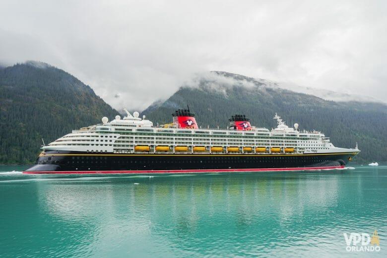 Foto do navio de cruzeiro da Disney em alto mar, com montanhas ao fundo
