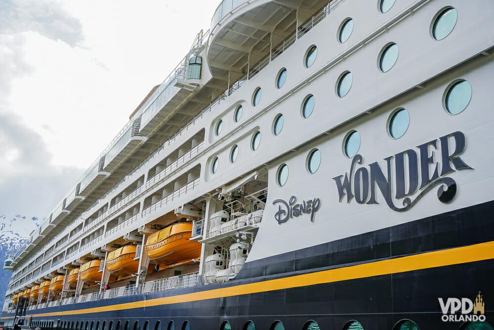 Navio da Disney Cruise Line parado no porto. O texto na lateral mostra que esse é o navio Disney Wonder.