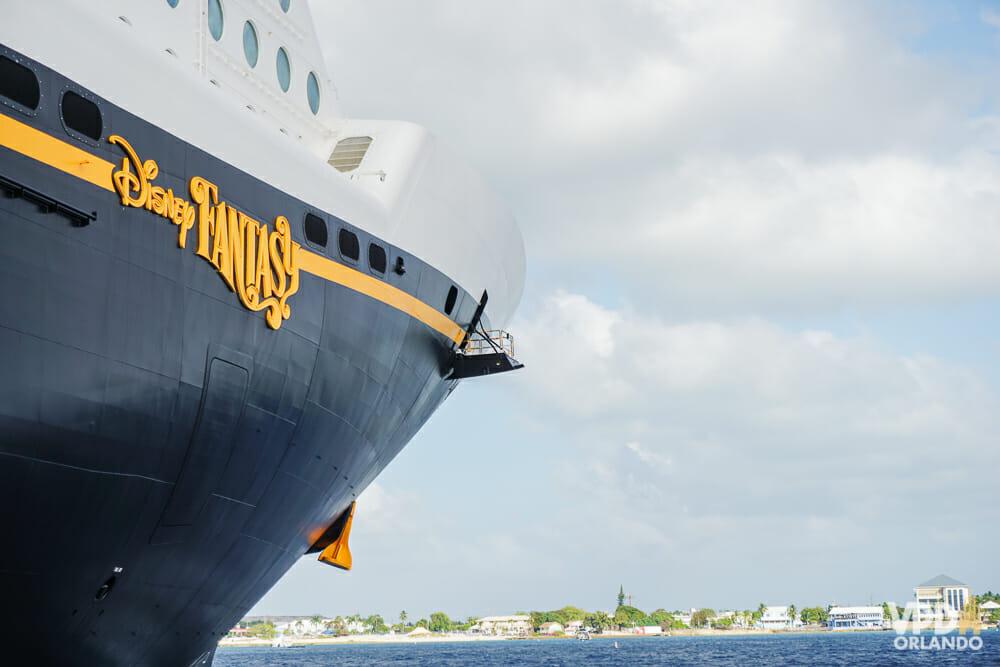Foto do navio de cruzeiro da Disney Cruise Line em alto mar, com o letreiro em amarelo na lateral indicando que é o Disney Fantasy