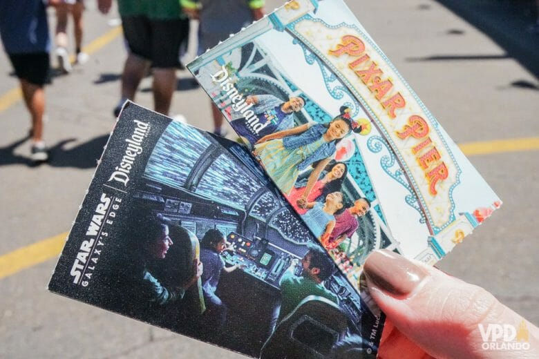Foto de uma mão segurando os ingressos dos parques da Disney na Califórnia. Um traz uma foto e texto do Pixar Pier, e outro uma imagem de dentro da Millennium Falcon em Galaxy's Edge. Os parques agora tem data para reabrir.