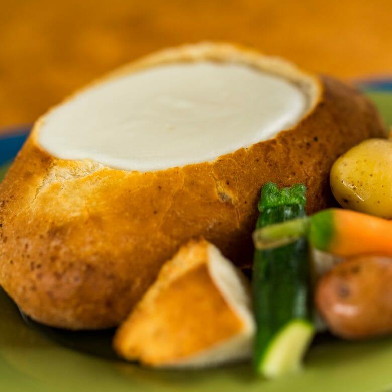Imagem de uma sopa dentro de um pão, com alguns vegetais do lado direito.