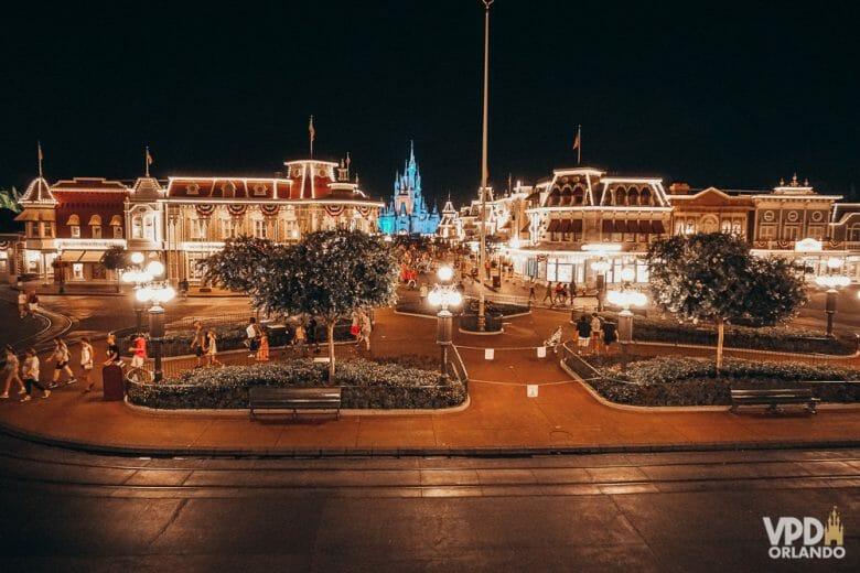 Imagem mostrando o início da Main Street no Magic Kingdom à noite. O parque está vazio, com algumas pessoas perto do castelo e outras saindo do parque.