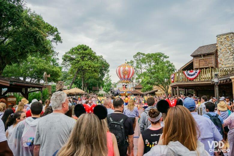 Imagem da Frontierland no Magic Kingdom, onde a parada da tarde está passando. Várias pessoas andam atrás do carro que leva o Mickey e a Minnie