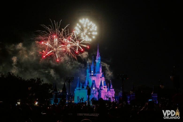 Castelo do Magic Kingdom à noite, iluminado de roxo e azul pelo show de fogos Happily Ever After, ainda sem data prevista para retorno em 2021.