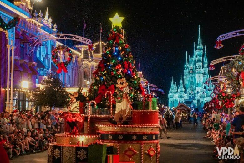 Parada de Natal do Magic Kingdom com Mickey em carro alegórico e castelo iluminado com luzes de Natal ao fundo. A semana do natal é uma das épocas para evitar visitar os parques por causa da lotação.