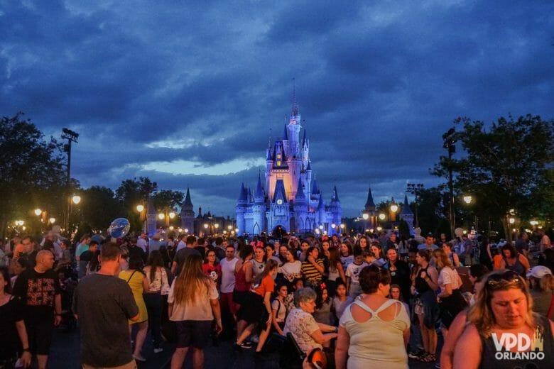 Imagem do Magic Kingdom à noite. A foto mostra o castelo iluminado de roxo e muitas pessoas em frente.