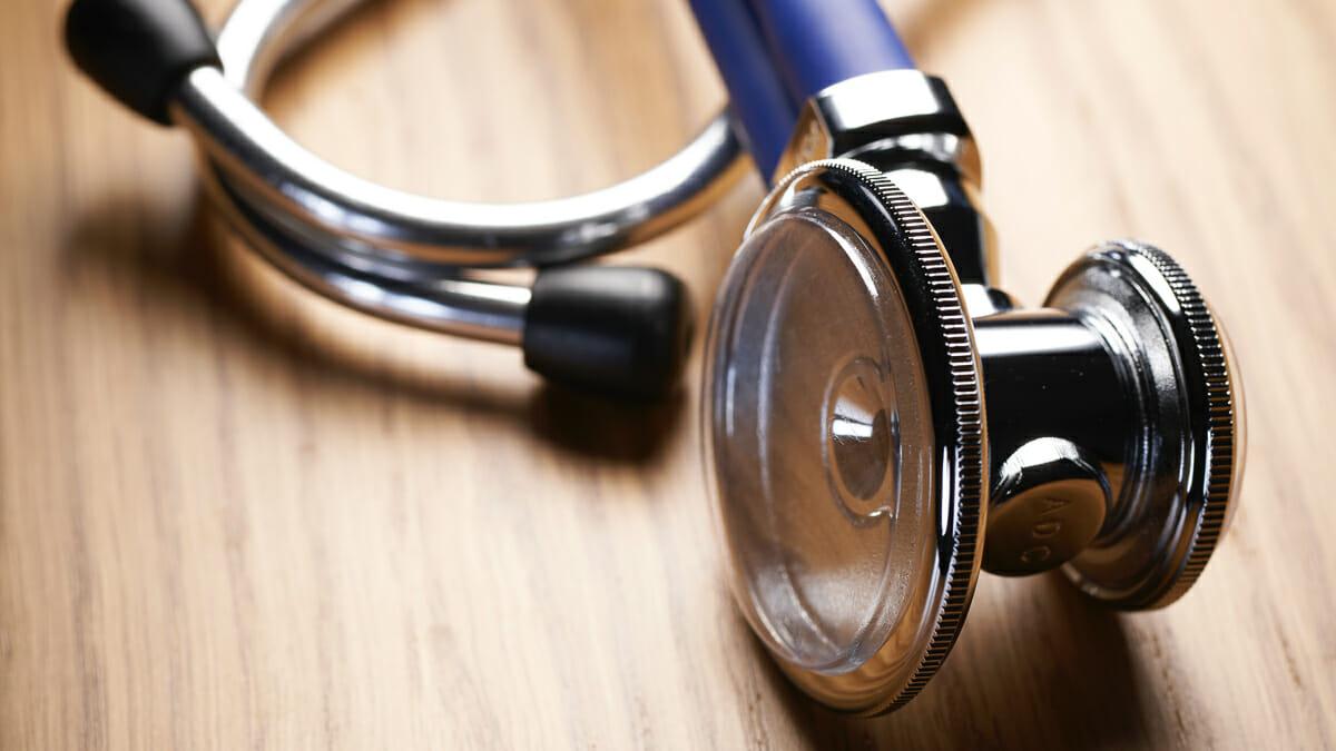 Imagem de um estetoscópio médico em uma mesa de madeira