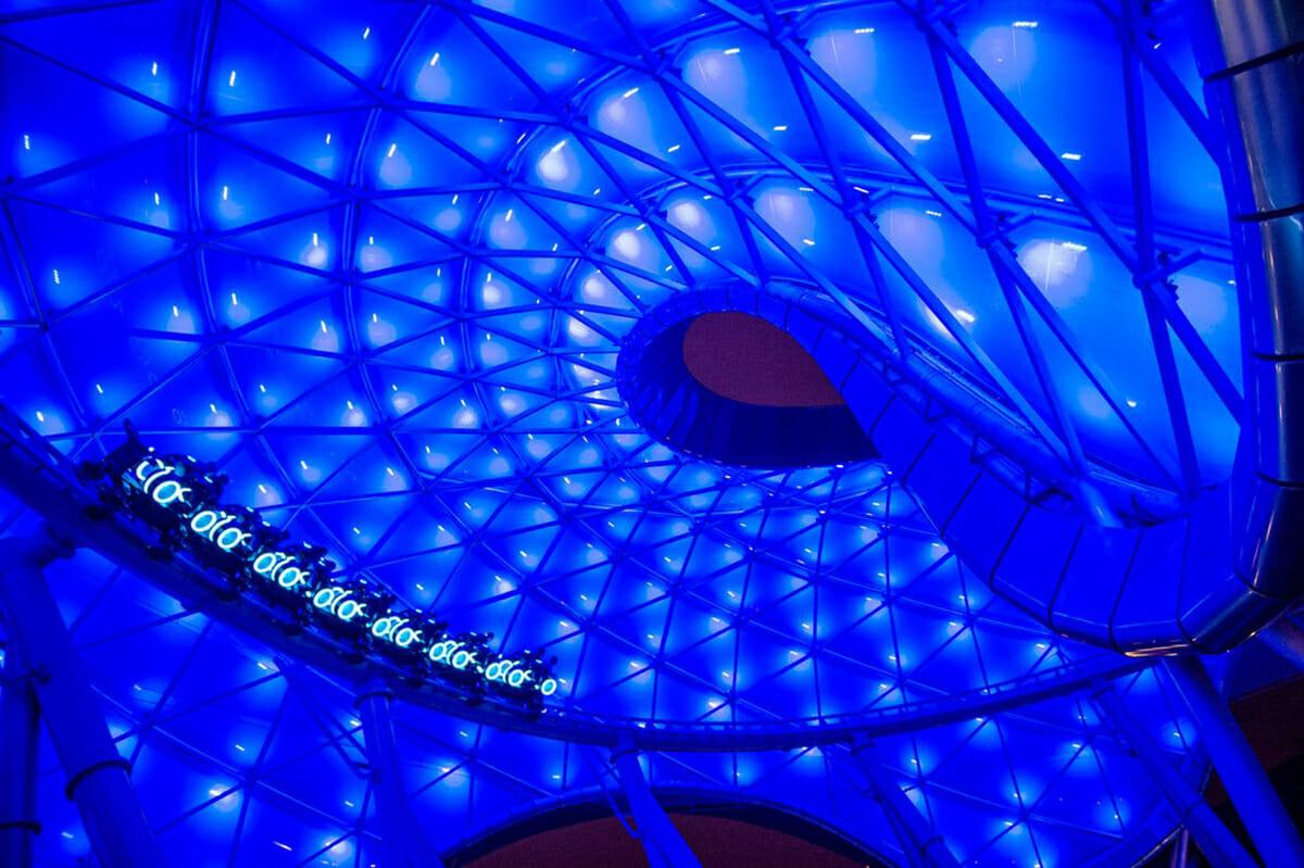 Foto da montanha-russa baseada no filme Tron, que vai abrir no Magic Kingdom. Ela é iluminada por luzes azuis e também tem um fundo azul.