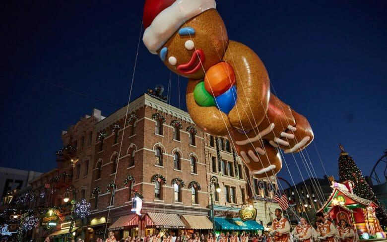 Foto de uma parada com balão em formato de Gingerbread Man, que faz parte das comemorações de Natal da Universal.