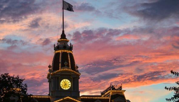 Imagem do topo do City Hall no Magic Kingdom durante o pôr do sol. Há uma bandeira com um desenho do castelo.