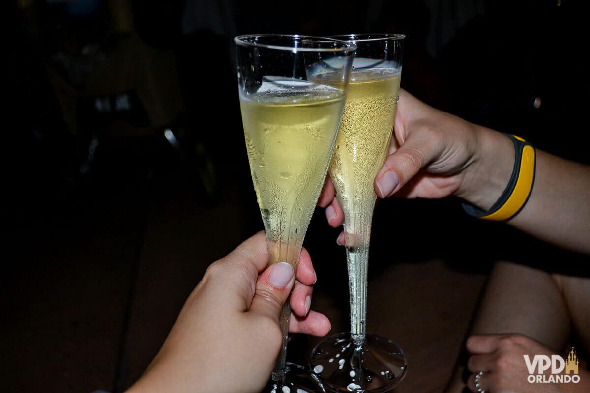 Imagem de duas mãos brindando com duas taças de champagne