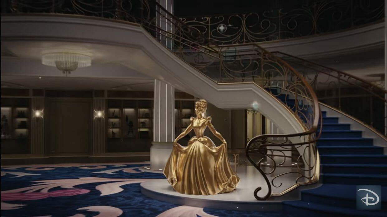 Imagem do novo navio Disney Wish, com estátua dourada da Cinderella ao lado da escadaria.
