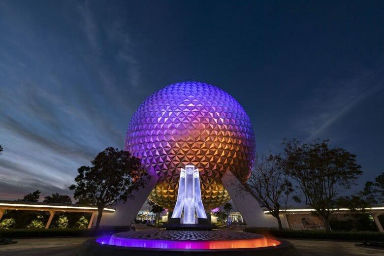 Imagem da nova fonte na entrada do Epcot durante à noite. A Spaceship Earth e a fonte estão iluminadas de roxo, rosa e laranja.