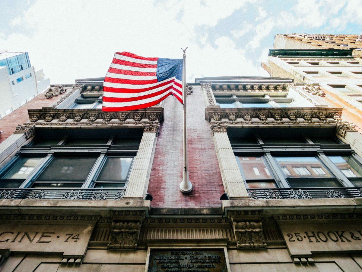 Foto de um prédio com uma bandeira dos Estados Unidos e o céu claro acima.
