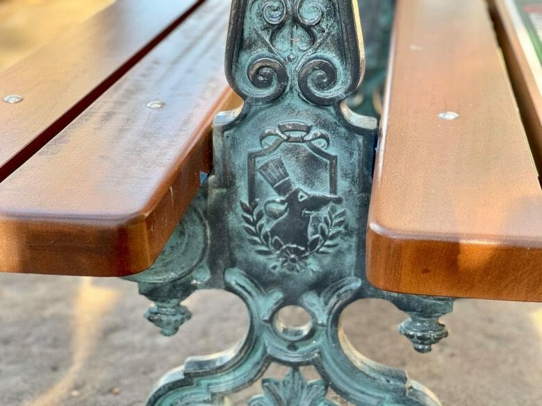 Detalhe de metal em um banco de madeira com um desenho do ratinho Remy. Esses bancos estão na expansão do pavilhão da França no Epcot.