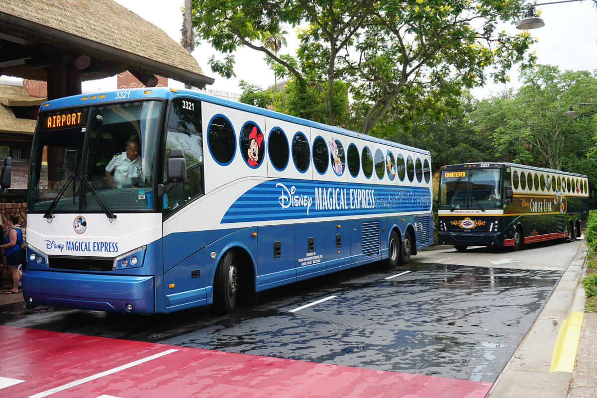 Imagem de dois ônibus estacionados. O que está na frente é azul e branco, traz personagens da Disney e o texto Magical Express.