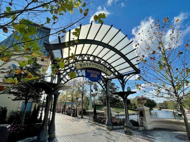Imagem do arco de entrada da nova área do pavilhão, com árvores e uma placa escrito Ratatouille. A expansão do pavilhão da França no Epcot foi inaugurada na semana passada.