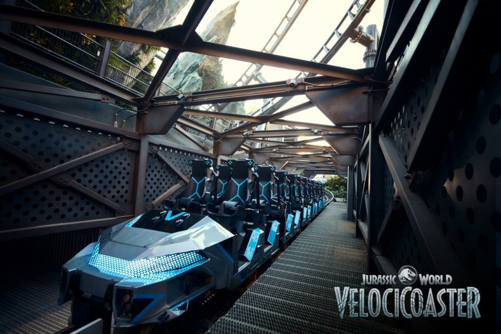 Foto do carrinho da VelociCoaster. Ele tem detalhes e luzes azuis e marcas deixadas pelos dinossauros.