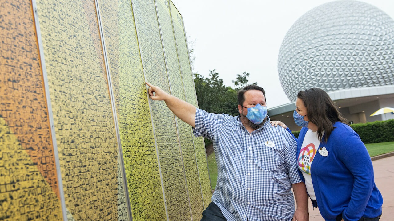 Imagem de dois visitantes em frente aos novos monolitos do Leave a Legacy, com a Spaceship Earth ao fundo. Ambos usam roupas azuis e usam máscaras também azuis.