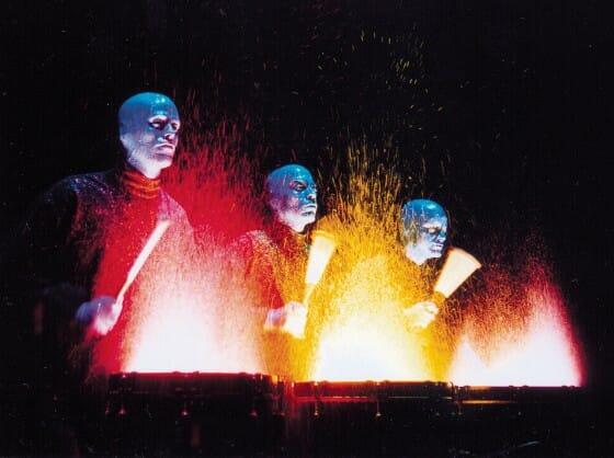 Foto do palco durante o show do Blue Man Group em Orlando. Eles estão tocando tambores com tinta em cima, espalhando-a por toda parte.