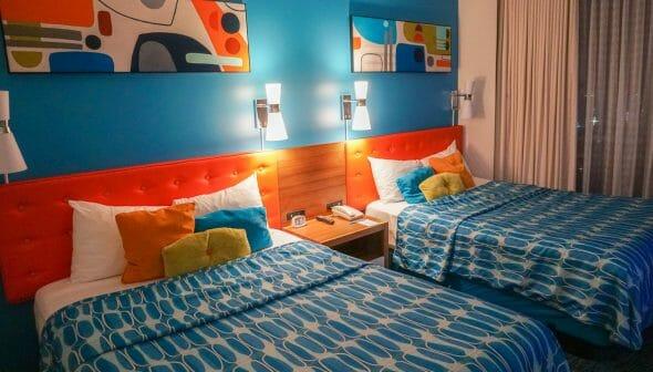 Imagem de duas camas no hotel Cabana Bay. A cabeceira é laranja, a parede é azul e as camas tem colchas azuis e almofadas coloridas.
