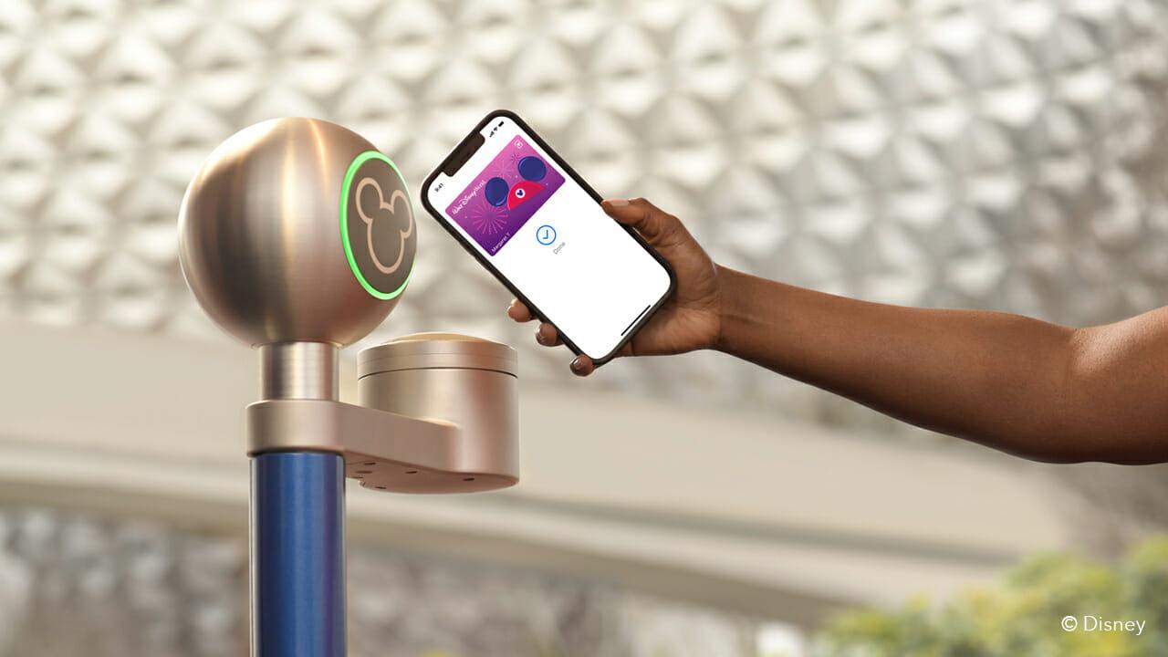 Imagem de um celular se aproximando do sensor na entrada dos parques da Disney, representando o MagicMobile.