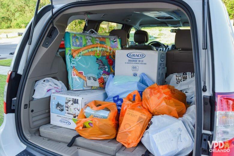 Imagem do porta-malas de um carro cheio de sacolas com compras de enxoval.