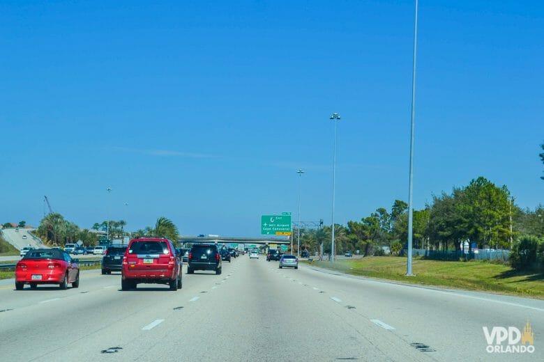 Imagem de uma rodovia em Orlando. Vários carros andam em 4 faixas, e há placas indicando o caminho à frente.