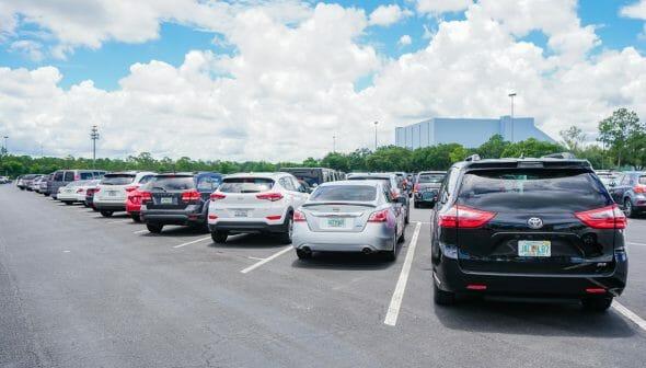 Imagem de um estacionamento, com vários carros parados nas vagas.