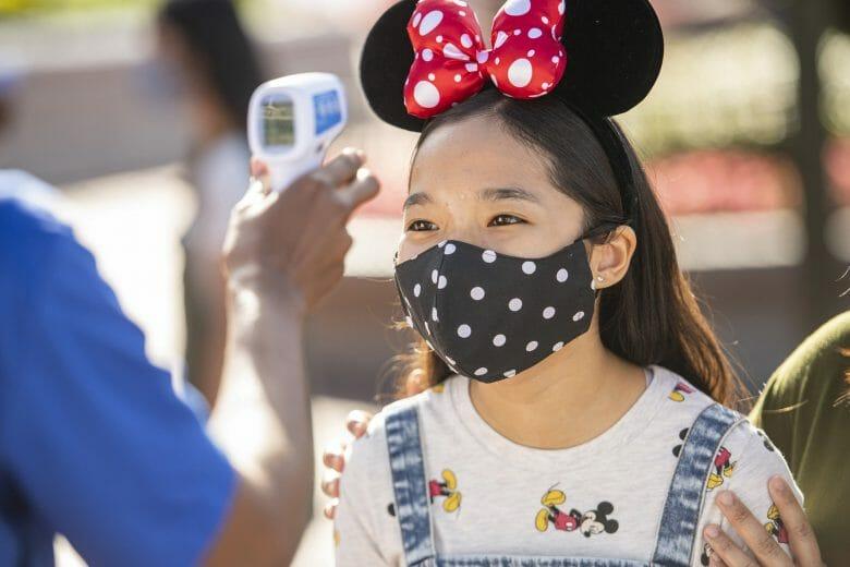 A Disney voltou a exigir o uso de máscaras em áreas internas. Uma menina tem a sua temperatura checada e usa uma máscara preta do Mickey.
