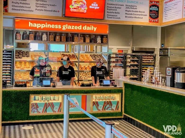 O balcão da loja. Há três funcionários no caixa que usam máscara e estão atrás de uma divisória de acrílico. Ao fundo, há vários donuts em uma vitrine.