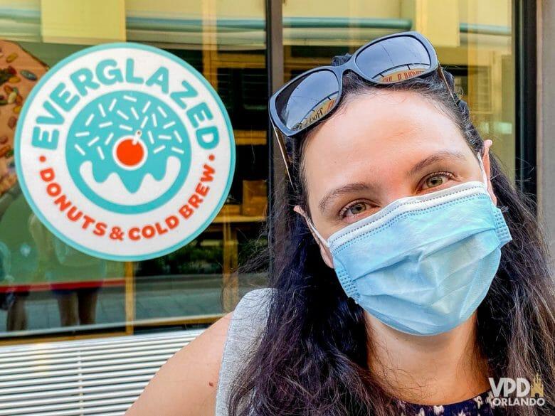 Foto da Renata, de máscara e óculos na cabeça, em frente à uma placa que diz Everglazed Donuts.