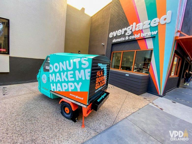 Entrada da Everglazed Donuts. A parede é preta com riscos coloridos. Há um caminhãozinho de entrega estacionado.