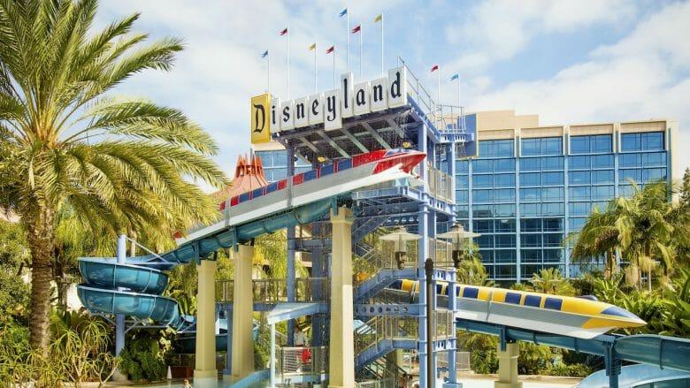 Imagem do Disneyland Hotel, com a torre de janelas espelhadas ao fundo e o logo do complexo na frente.