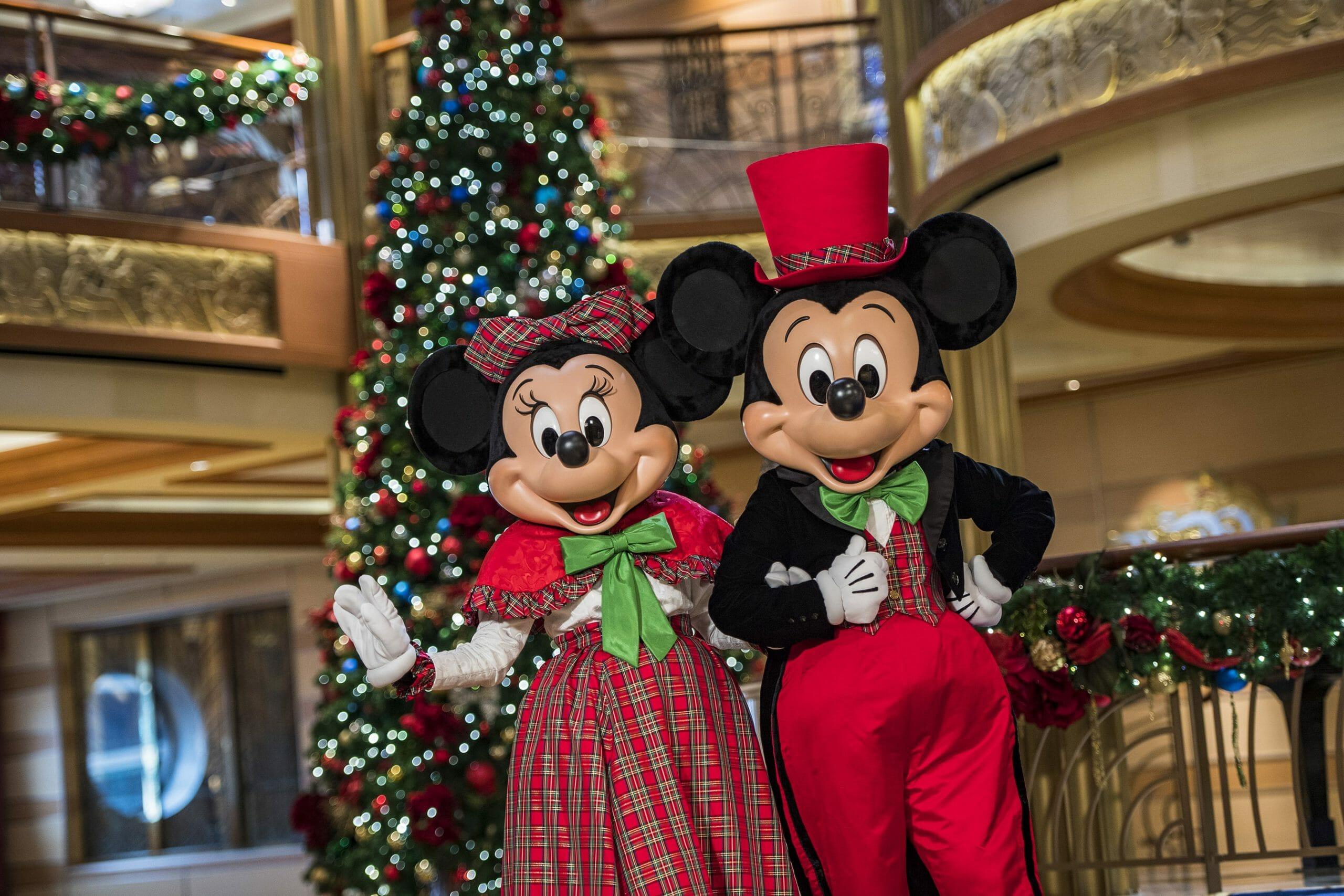 Mickey e Minnie com roupas de Natal em frente a uma árvore de Natal no átrio do navio de cruzeiro da Disney