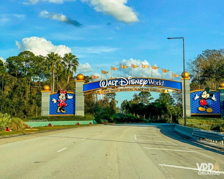 Imagem do portal de entrada da Disney, que foi reformado para o aniversário de 50 anos. Ele é azul escuro, cinza e tem detalhes em dourado. O Mickey está do lado direito e a Minnie do lado esquerdo.